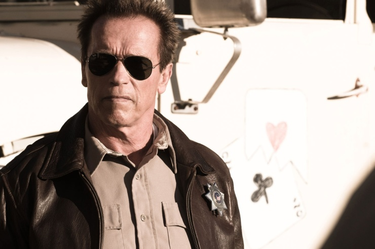 Sheriff Ray Owens (Arnold Schwarzenegger) stands around looking a bit tough and a bit old.